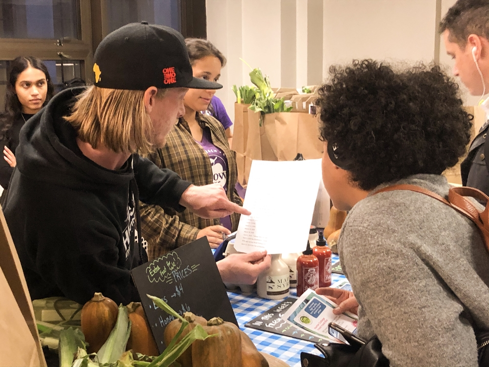 A GrowNYC representative shows a student a schedule for the Fresh Food Box