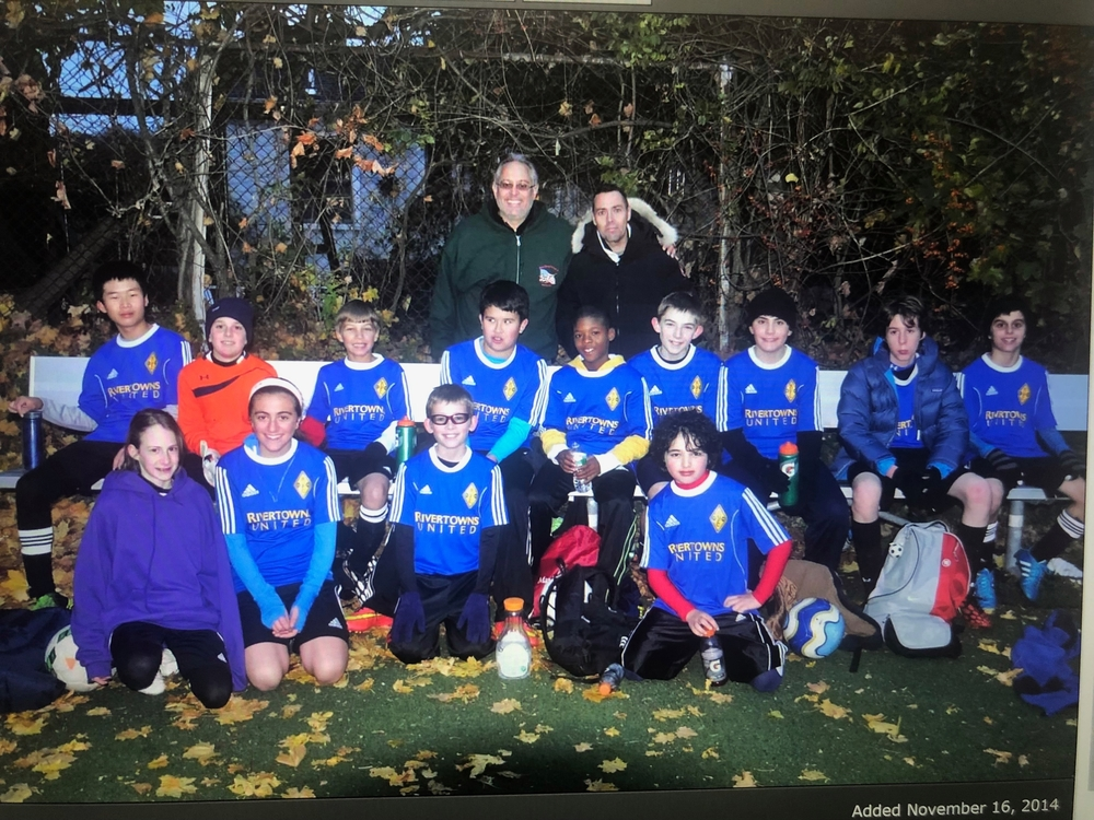 A group photo of the RUFC boy's club team. Abirizk and another girl are sitting in the lower left.