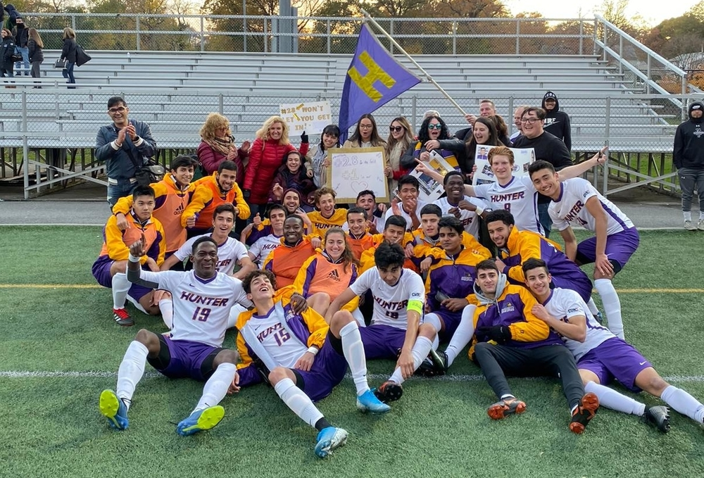 A group photo of the Hunter College men's soccer team, along with coaches and family members. Abirizk sits in the middle front.