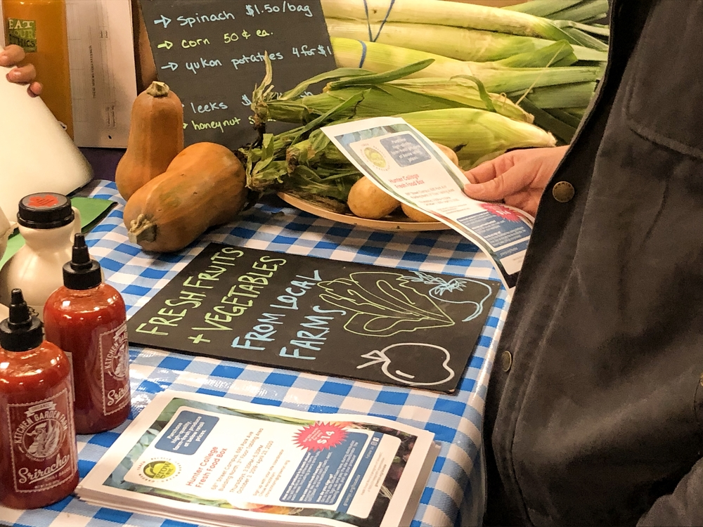 A man's hand holding a flyer next to the Fresh Food Box stand at Hunter North
