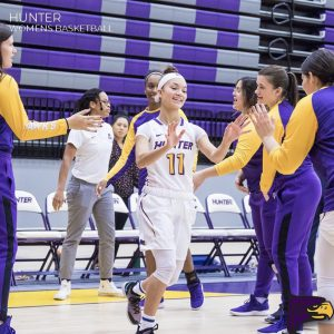 Jade Aponte high-fiving her teammates coming onto the court for her final home game