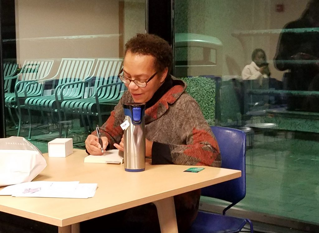 """Lauret Savoy signs copies of her book, """"Trace: Memory, History, Race, and the American Landscape."""""""